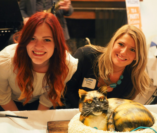 Moxley Carmichael interns Lindsey Collins, left, and Savanna Howie, enjoyed a 3D replica cake of Rexie - the beloved cat of Cynthia Moxley - at Moxley's 60th birthday party earlier this year. Collins is now with the International Biscuit Festival in Knoxville, and Howie has accepted a job with a public relations firm in Nashville.